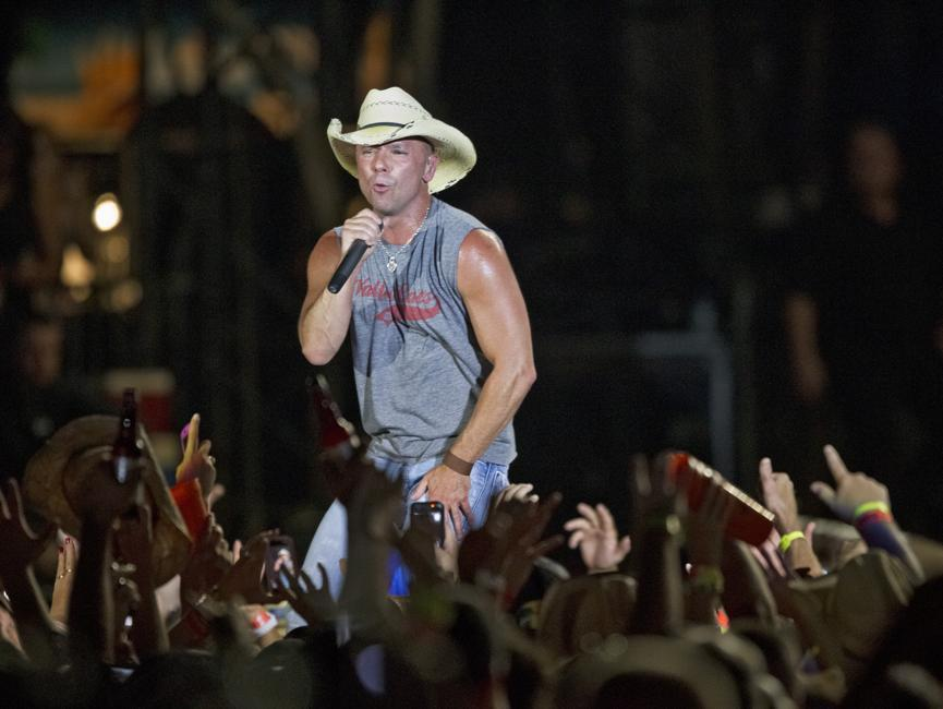 Kenny Chesney fans raise beer bottles to the singer at an August concert in Foxborough.